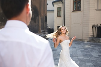 Bride dancing in the street while her husband watches