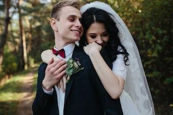 Bride hugging groom standing in woods