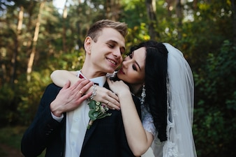 Bride hugging smiling fiance standing in woods