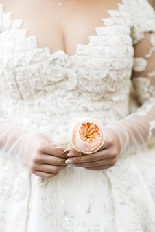 Bride in rich dress holds beige boutonniere