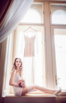 Bride in white stockings sits on windowsill before bright window