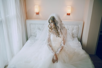 Bride kneeling on the bed with his hands clasped