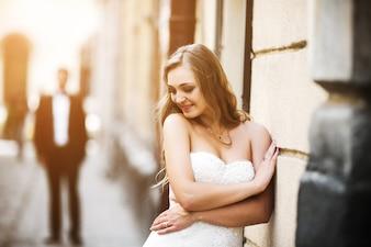 Bride leaning on wall and boyfriend behind defocused