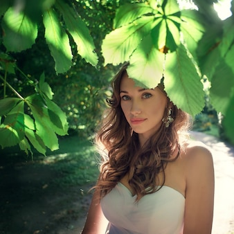 Bride poses under chestnut tree