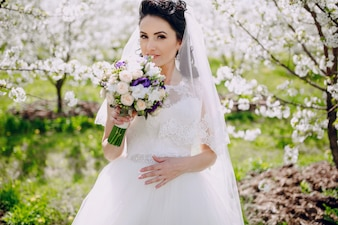 Bride smelling her bouquet with flowering trees background