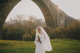 Bride smiling under a bridge
