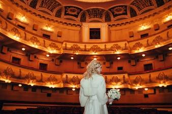 花嫁は劇場の古いホールで新郎を待つ