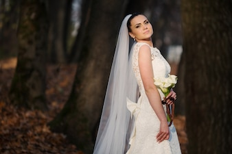 Bride with a bouquet in a forest