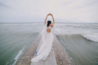 Bride with arms raised at sea