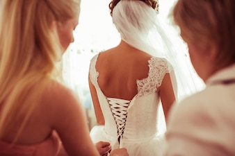 Bridesmaid climbing the zipper of a wedding dress