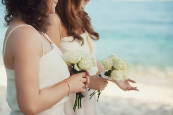 Bridesmaids holding bouquets wearing dresses
