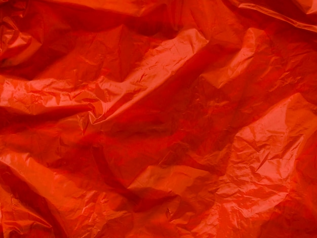Bright red crumpled plastic bag background