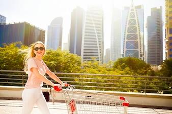 ショッピングカートに立っているかわいらしい女性の上に明るい太陽が輝きます