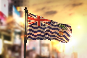 British Indian Ocean Territory Flag Against City Blurred Background At Sunrise Backlight