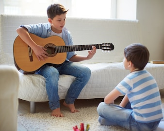 Brothers playing guitar