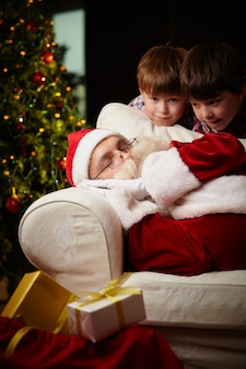 Brothers with santa asleep on the couch