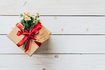 茶色のギフトボックスと花は木製のテーブルにプレゼント、母の日のコンセプト。
