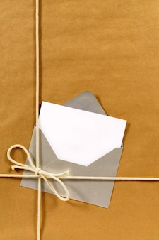 Brown paper parcel with envelope and blank message card