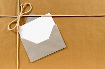 Brown paper parcel with envelope and message card