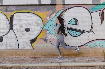ストリートで走っているブルネット少女
