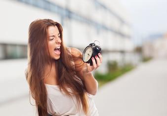 Brunette girl screaming at clock in hand.