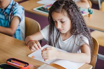 学校の机に座っているブルネットの女の子