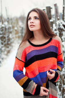 Brunette girl wearing a colorful pullover in the snow