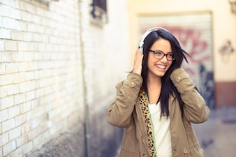 Brunette girl with glasses listening to music with headphones