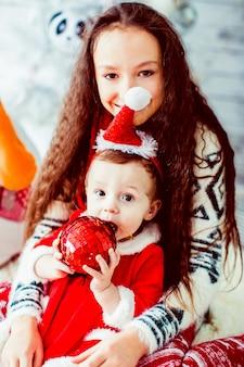Brunette girl with little sister posing