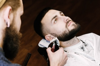 Brunette man lies with open eyes while barber cuts his beard