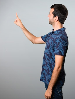 Brunette man touching on transparent screen on grey background
