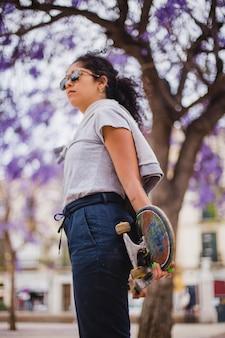Brunette teenage girl holding skateboard standing outside