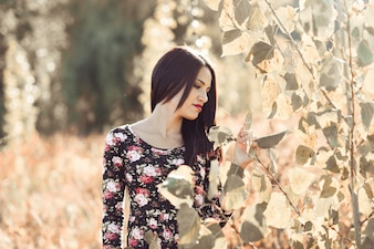 Brunette woman touching some leaves in the field