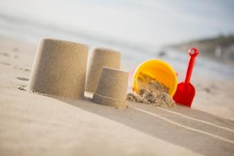 Bucket, spade and sand castles on beach