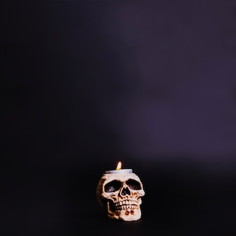 Burning candle in skull
