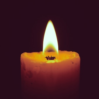 Burning candle on black with retro filter effect