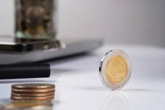Busines, finance, money and bookkeeping concept - coins on office table.