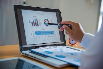 Business analysis - calculator, sheet, graphs (business report) and analyst hand