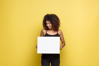 Business Concept - Close up Portrait young beautiful attractive African American pointing finger to plain white blank sign. Yellow Pastel studio Background. Copy space.