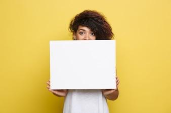 ビジネスコンセプト - クローズアップ肖像画の若い美しい魅力的なアフリカンアメリカンプレーン白い空白の看板を示す笑顔。イエローパステルスタジオの背景。スペースをコピーします。