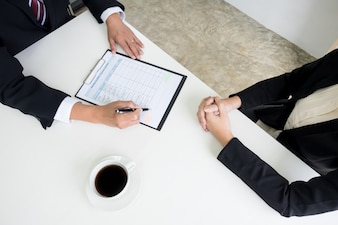 Business concept - Executives at desk discussion sales performance in a office