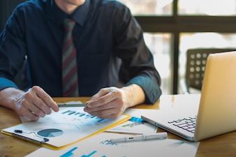オフィステーブル上のビジネス文書とソーシャルネットワークダイアグラムを持つグラフビジネスと、バックグラウンドで働く男性。