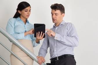 Business Man and Woman Using Tablet on Stairs