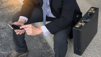 Business man wearing black suit and using modern smartphone in outdoor