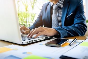 ラップトップ、タブレット、グラフのデータドキュメントをオフィスで机の上で働くビジネスマン