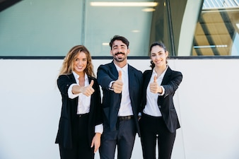 Business people making thumbs up gesture