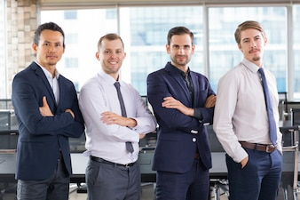 Business people with arms crossed and one with hands in pockets