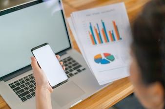 ビジネスの女性の手の金融チャートとテーブル上のラップトップを介して携帯電話。