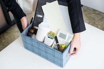 彼女が退職を決定し将来仕事を変えるときに個人の会社の財産を梱包するビジネスマン
