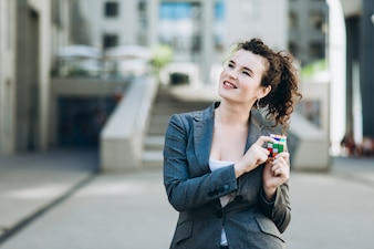 Business woman plaing with the Rubik's Cube